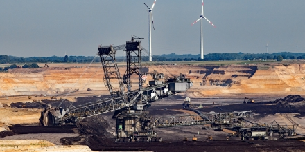 Open pit coal mining with alternative energy wind turbines.